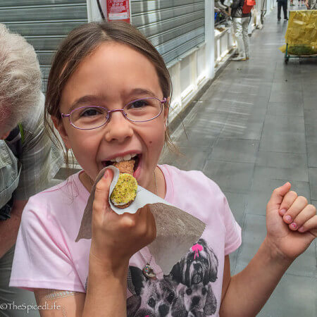 Child eating a connolo on food tour in Rome