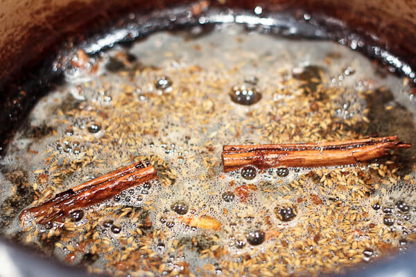 Cinnamon sticks, cumin seeds and other spices roasting in oil for an Indian curry