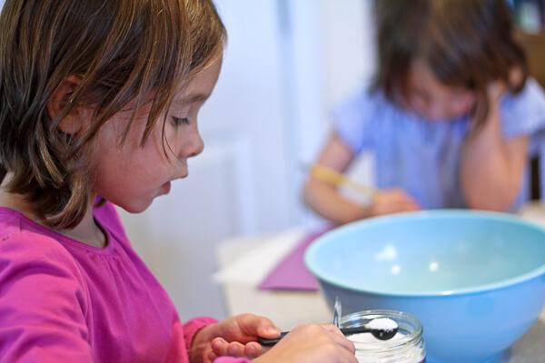 child measuring salt for baking, using knife to level