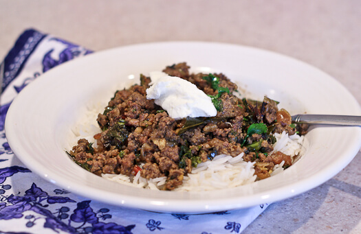 Greek yogurt on Indian kheema curry with greens