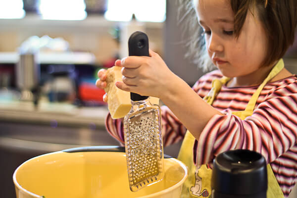 child grating parmesan cheese for meatballs