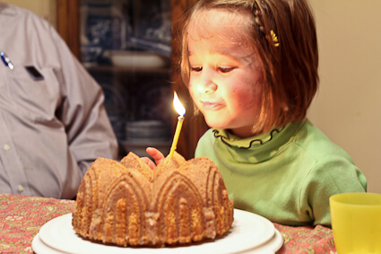Child blowing out birthday candle on Moroccan Inspired Bundt Cake
