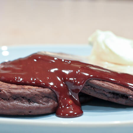 Hot Chocolate Sauce cascading down Triple Chocolate Pancakes