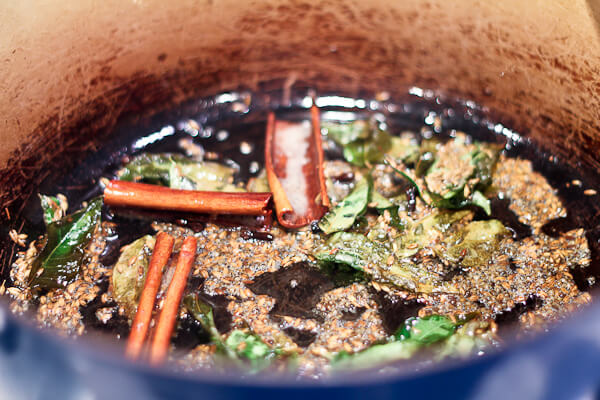 Roasting whole spices such as cinnamon, cumin and mustard seeds and curry leaves for pumpkin dish