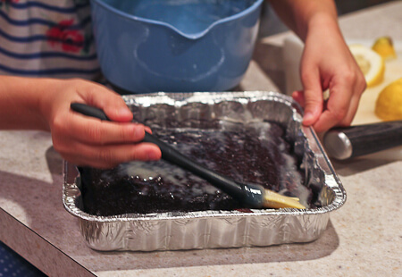brushing buttermilk glaze onto chocolate cake
