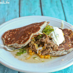 Braised Brisket with Corn and Shredded Cheese on Bacon Ricotta Corn Cakes