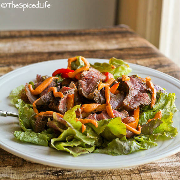 Marinated steak salad with roasted peppers and onions, and a tangy Romesco dressing.