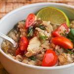 Arroz Caldo (Filipino Chicken and Rice Porridge) garnished with tomatoes, cilantro and lime